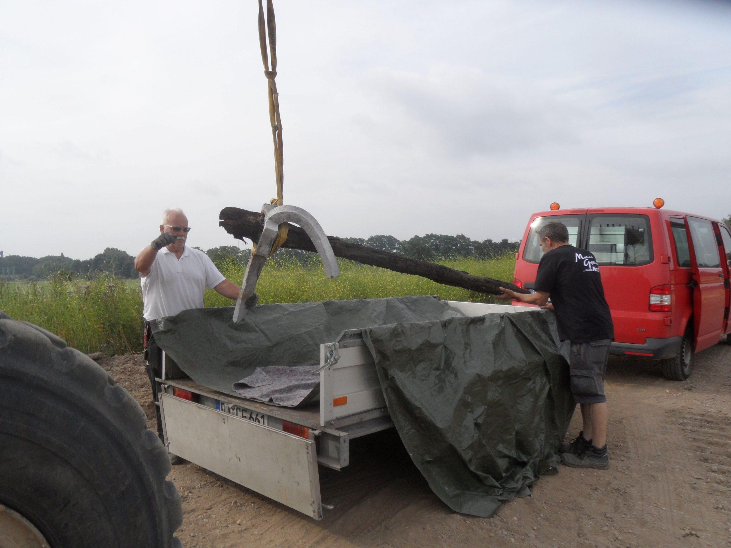 Der 1,36m lange Anker wird mit Hilfe eines Seitzuges auf einen Autoanhänger gehoben. Zwei Herren stehen dabei und überwachen das Ganze, einer von ihnen telefoniert und der andere stützt den Anker vorsichtig mit seinen Händen ab