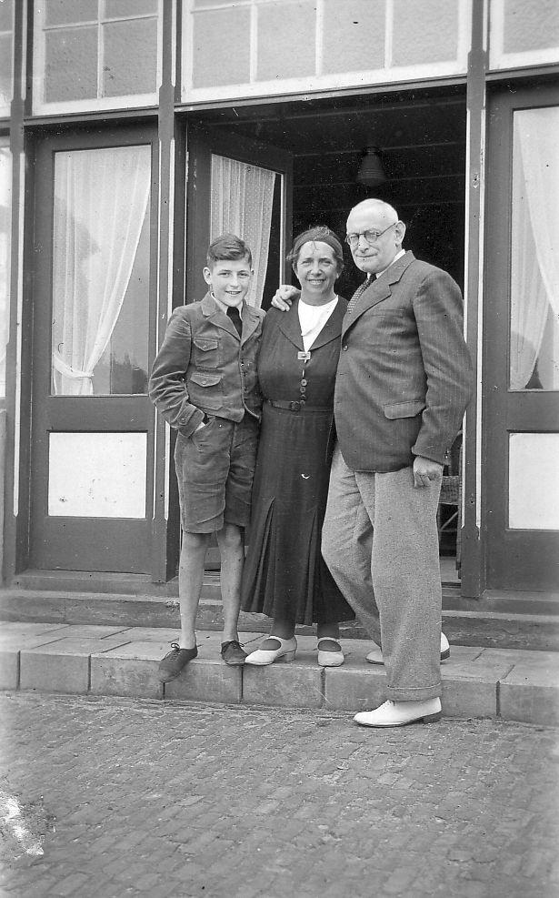 Ein Junge in kurzer Hosen und Jackett steht neben einer Frau mittleren Alters im langen Kleid und einem ebenfalls älteren Herrn. Sie stehen augenscheinlich vor einem Geschäft und lächeln zufrieden in die Kamera..