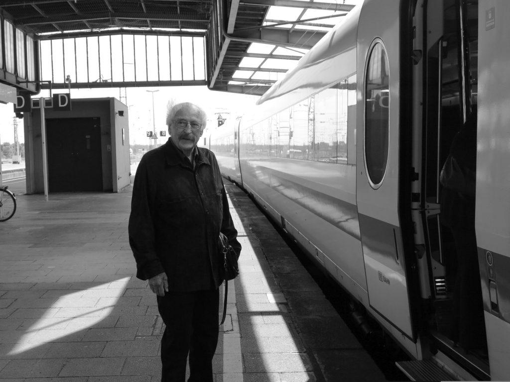 Ein älterer Herr steht am Bahnhof neben einem Schnellzug